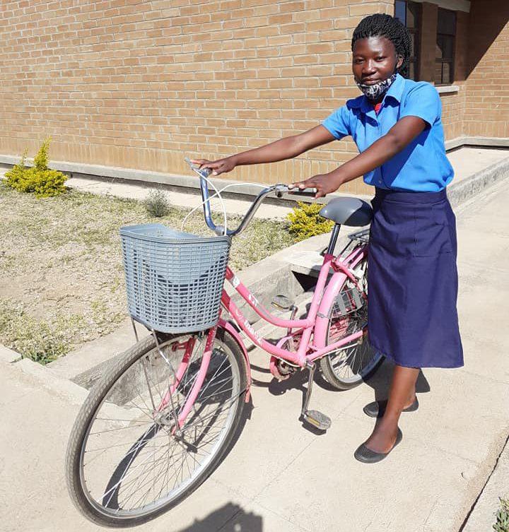 Meisje met mondkapje en fiets